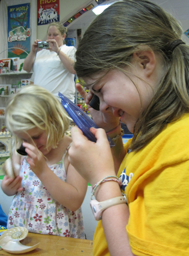 Kids using Private Eyes to examine snails and a shell